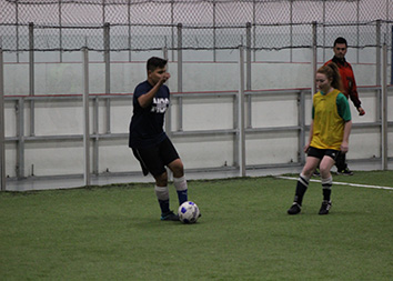 MCC player kicking soccer ball